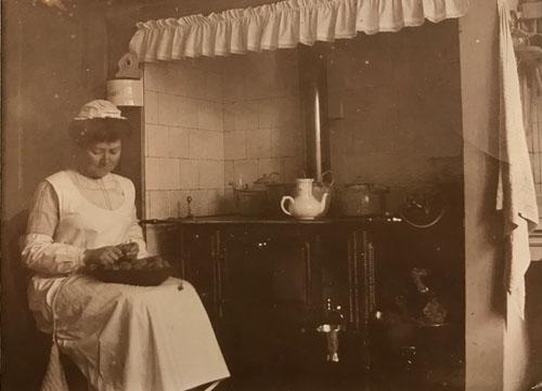 Angelique Dumont schilt aardappelen voor een ouderwets fornuis, begin 20e eeuw